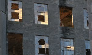 The setting sun lights a window in one of the old disused mill buildings on the Cowgate in Dundee