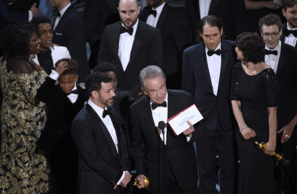 Presenter Warren Beatty shows the envelope with the actual winner for best picture as host Jimmy Kimmel, left, looks on at the Oscars on Sunday,