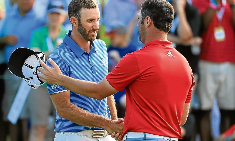 Dustin Johnson shakes hands with Jon Rahm of Spain.