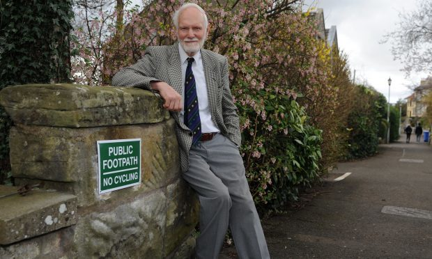 David Middleton of Lade Braes Walk in St Andrews next to one of his signs.