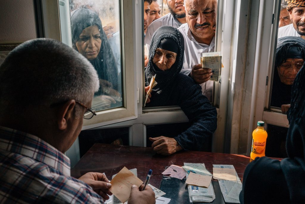 Displaced persons in Iraq reach through a window of a distribution centre where cash donations are made. Each registered civilian displaced by conflict receives a donation of 400USD.