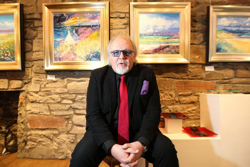 Jolomo with some of his artwork at Dundee's Gallery Q.