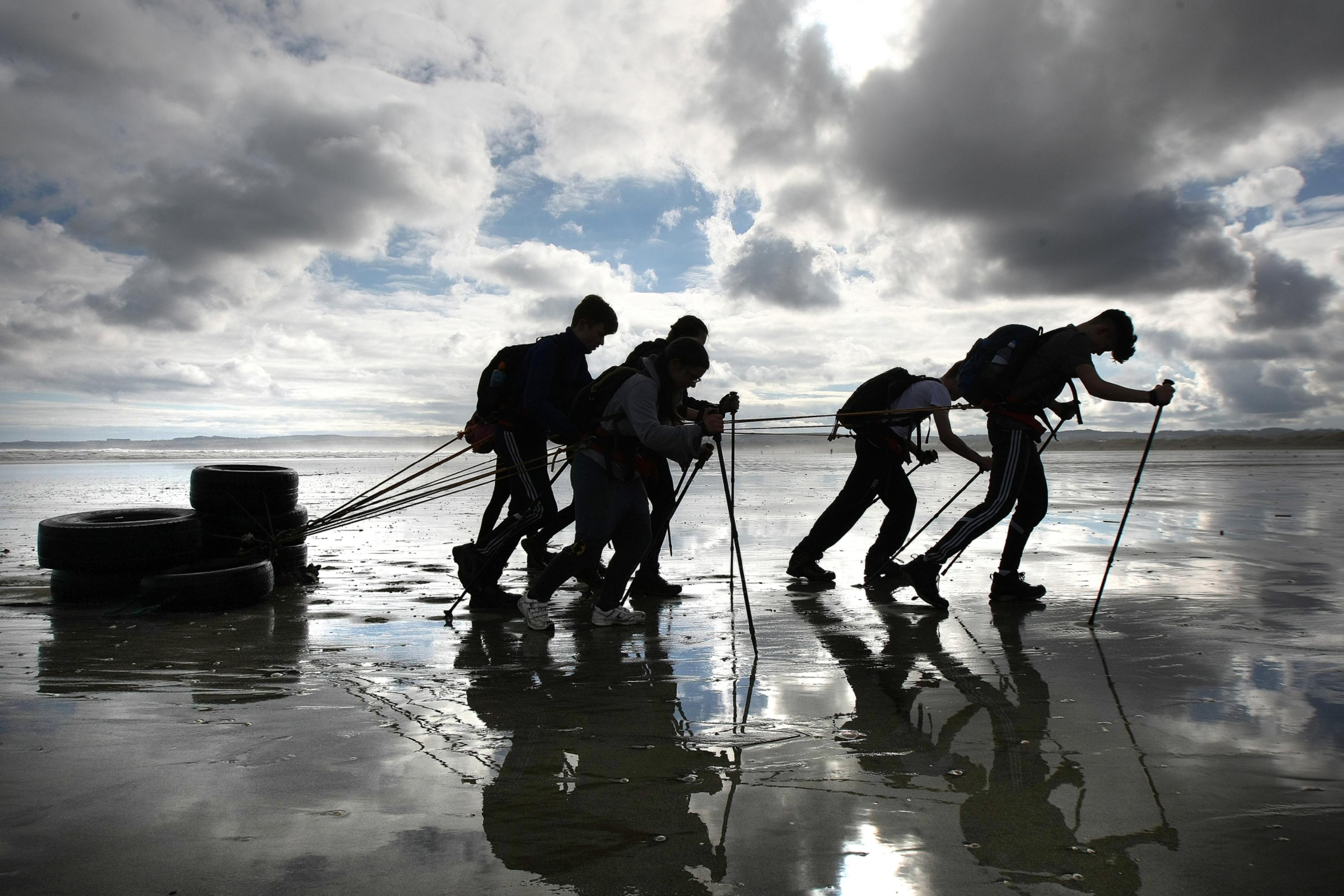 Tough work! Teenagers haul heavy tyres across West Sands, St Andrews.