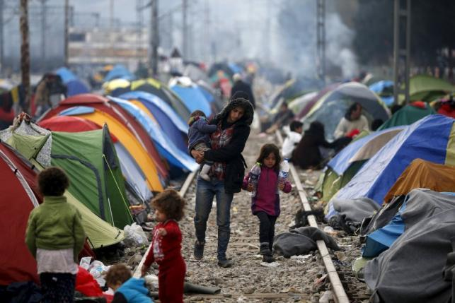 Migrants walk on a railway track at a makeshift camp on the Greek-Macedonian border, near the village of Idomeni, Greece March 12, 2016.