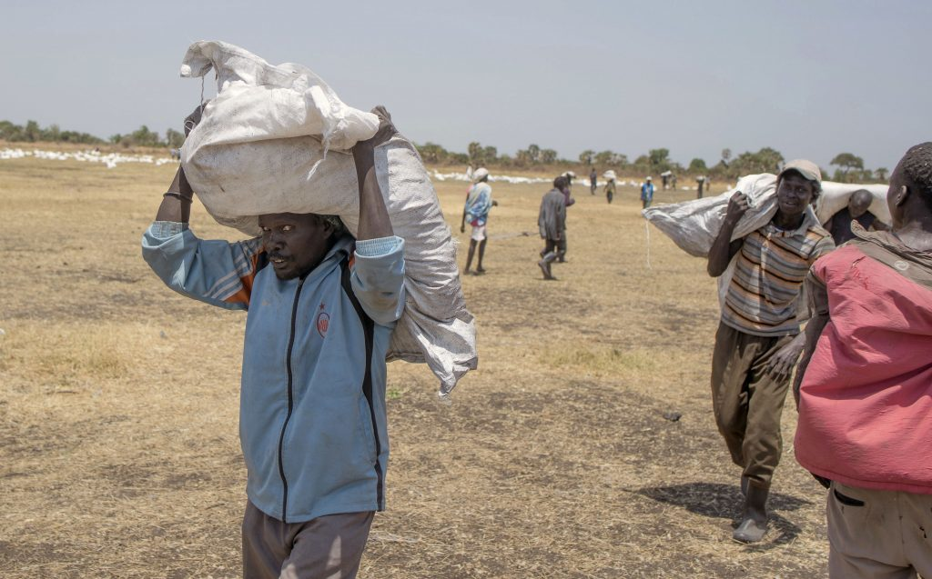 South Sudanese men carry food distributed by the World Food Programme in Leer County Southern Leich State in South Sudan where millions are on the brink of starvation. What difference would Scottish independence make to them?