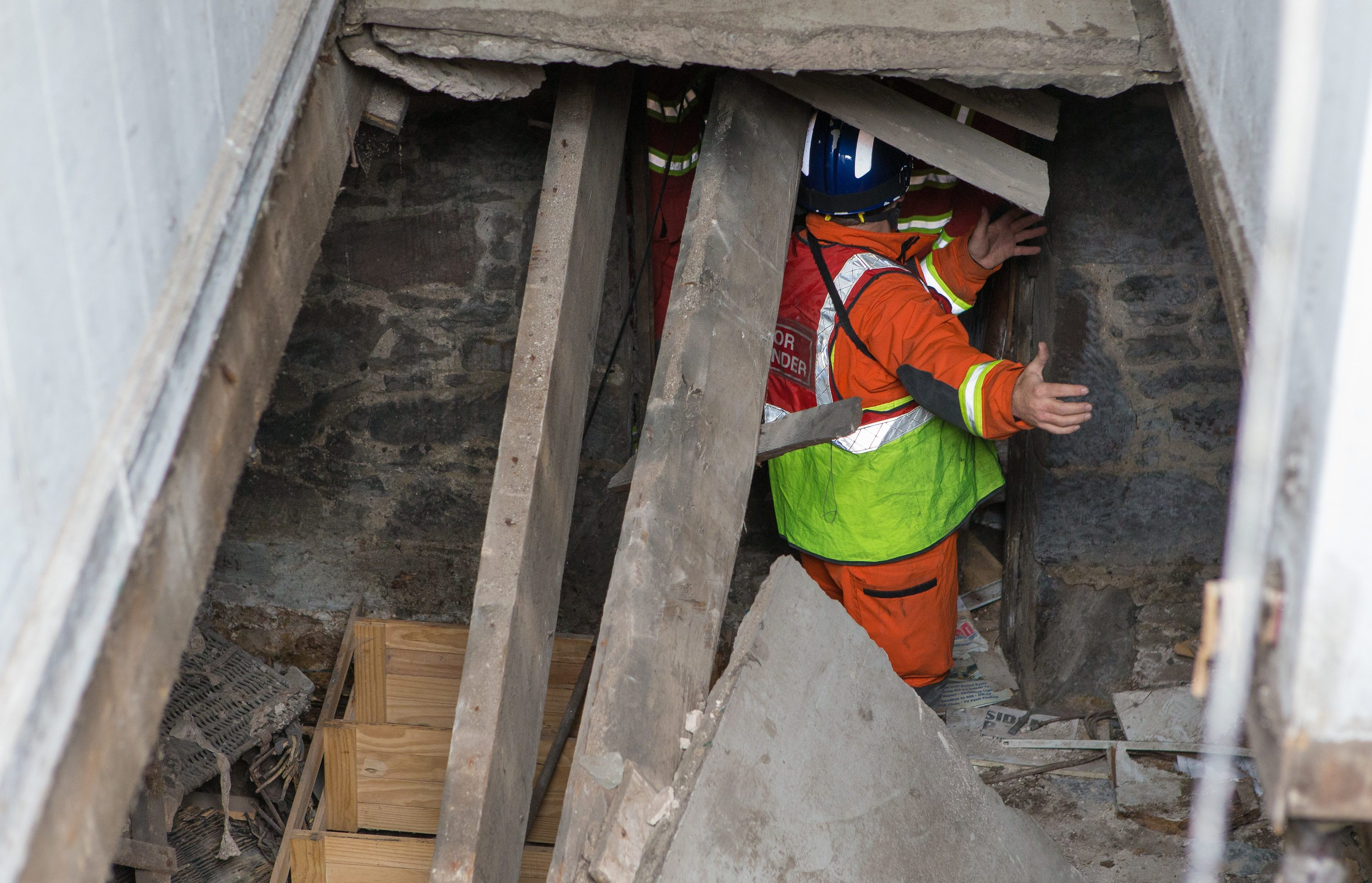 Emergency services examining the collapsed stairwell.