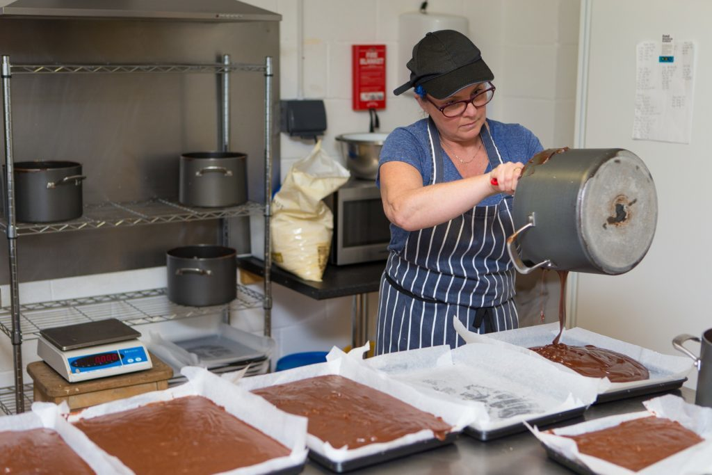 Staff member Eileen Dall pouring the fudge.