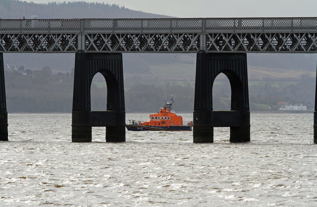 The Broughty lifeboat scours the area around the rail bridge.