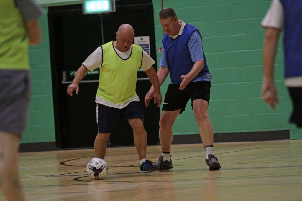 Men in action playing walking football.