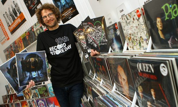 Andy McLaren - Manager of Assai Records in Broughty Ferry, holding copies of two exclusives, on the left, Carousel - Show The World, the first recording on the  Assai label, and The View - Hats Off To The Buskers.
