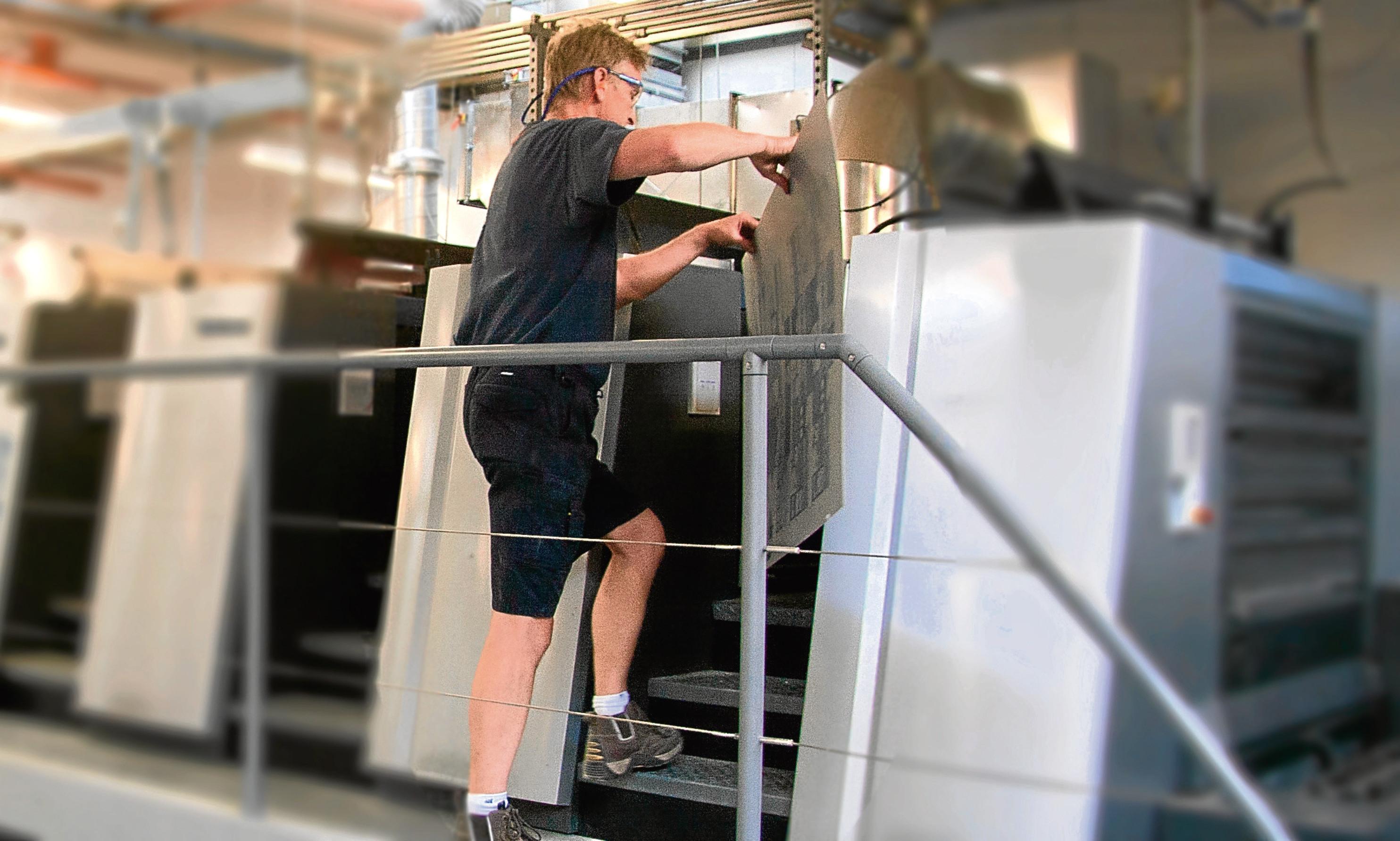 A Tradeprint technician puts a proof on a printing press