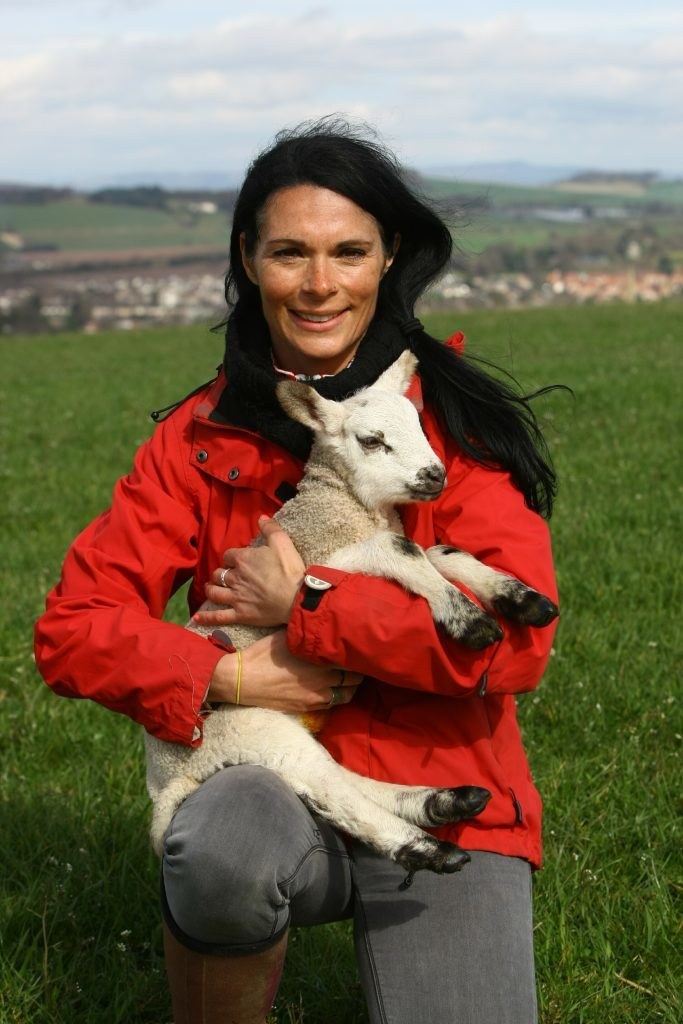 Gayle cuddling a little lamb.