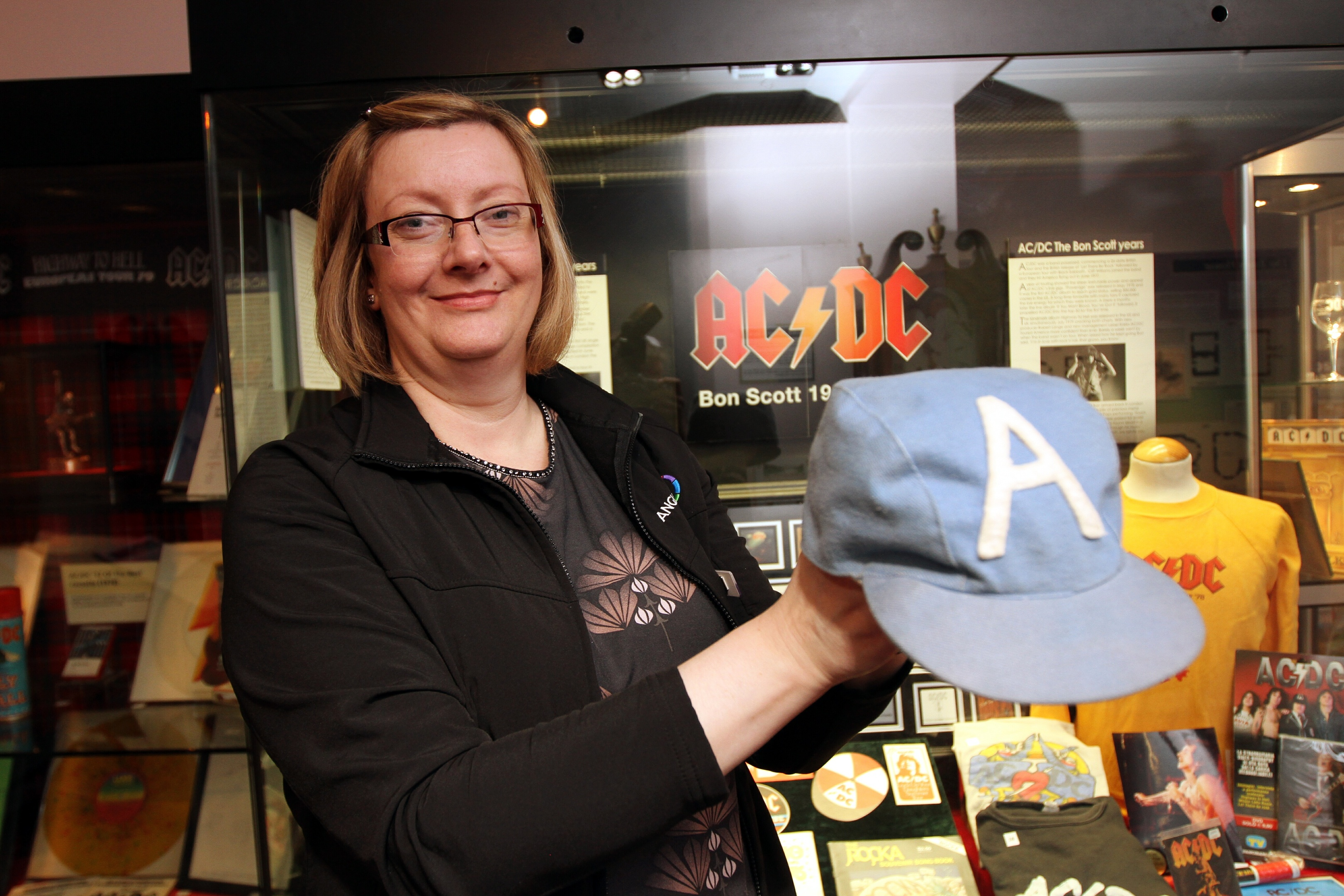 Museum officer Rachel Jackson with Angus Young's cap from 1976