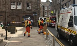 Specialist fire fighters leaving the council offices with the suspect package in a brown evidence bag
