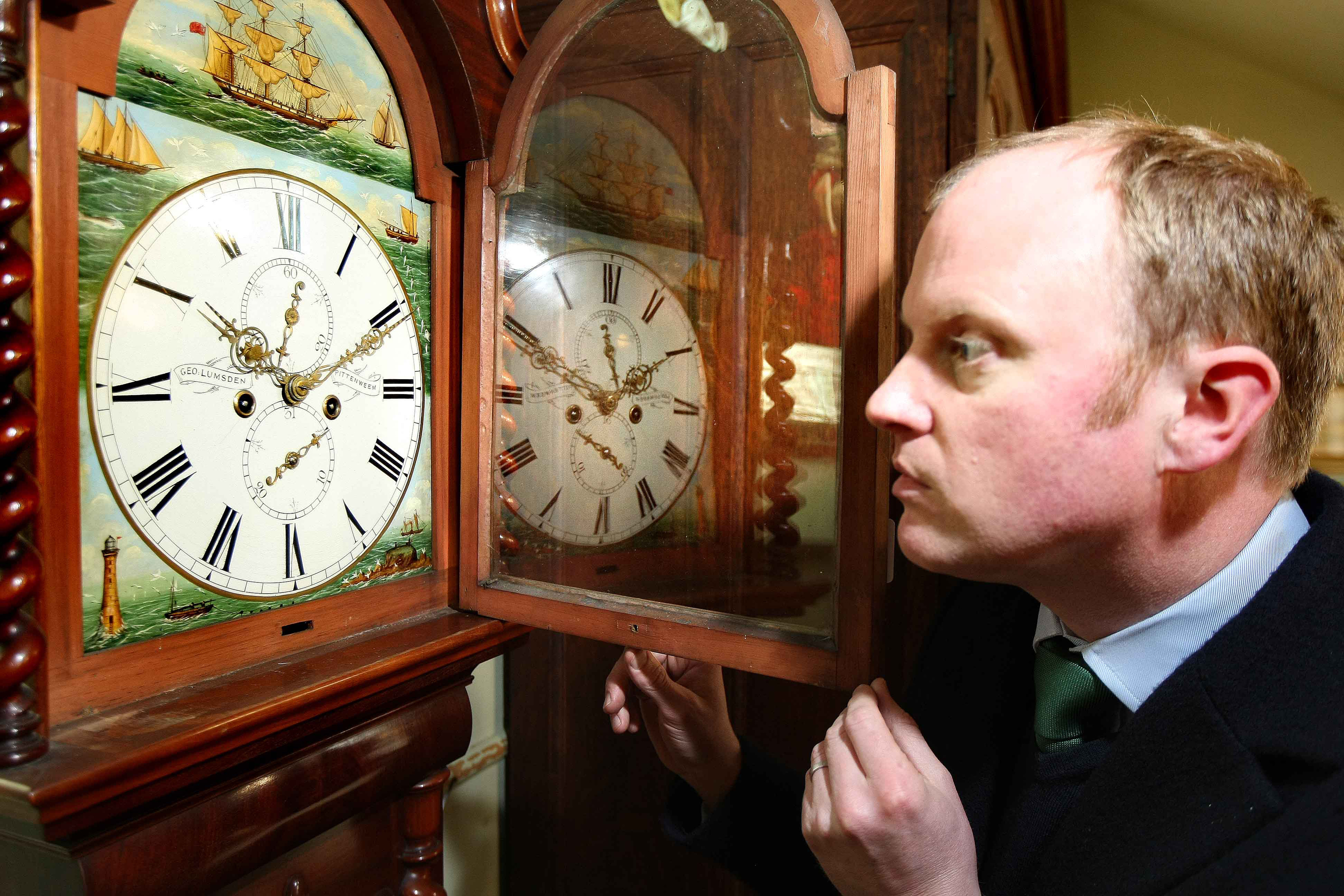 Auctioneer Nick Burns admires the detail on the George Lumsden of Pittenweem clock.