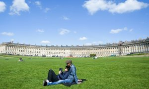 People relax in the sunshine on the lawn in front of the Victorian Royal Crescent, Bath.