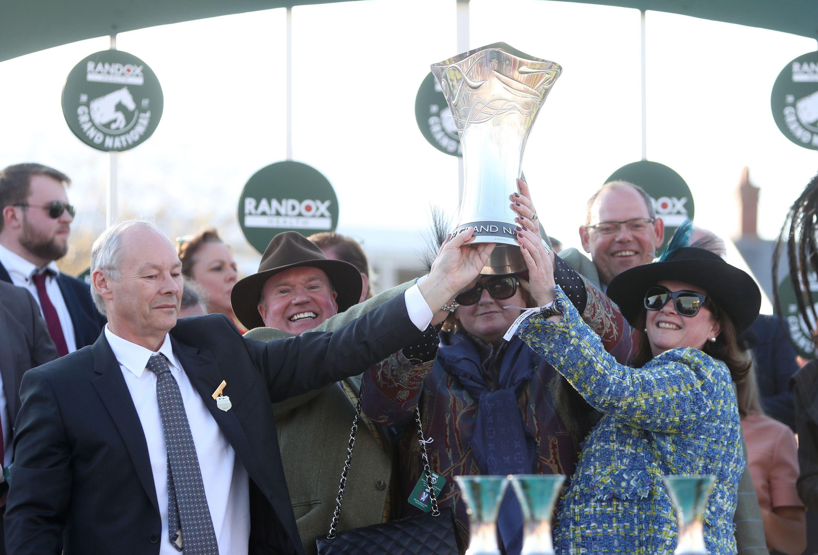 Belinda and Debs lift the trophy with husbands Colin (left) and Fraser (back, right).