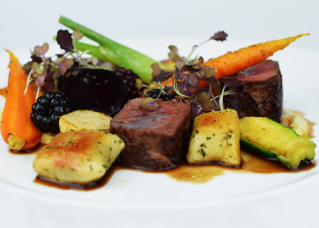 Venison loin with rosemary gnocchi, roast baby vegetables and blackberry jus.