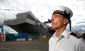 Courier News - PrinceCharles - Aircraft Carrier - Babcock - Rosyth. Prince Charles visiting aircraft carrier named after himself. Which will be nice. Hell be touring the ship, meeting dockyard workers before striking a gavel that places the final piece in to the flight deck. Picture shows; AB Iain Harris in HMS Prince of Wales cap in front of the ship, Monday 20 June 2016.