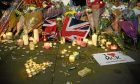 Candles and floral tributes are seen after a vigil outside Manchester Town Hall in the aftermath of the attack on Manchester Arena.