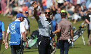 Former US president Barack Obama waves to spectators during a round of golf at St Andrews Old Course.