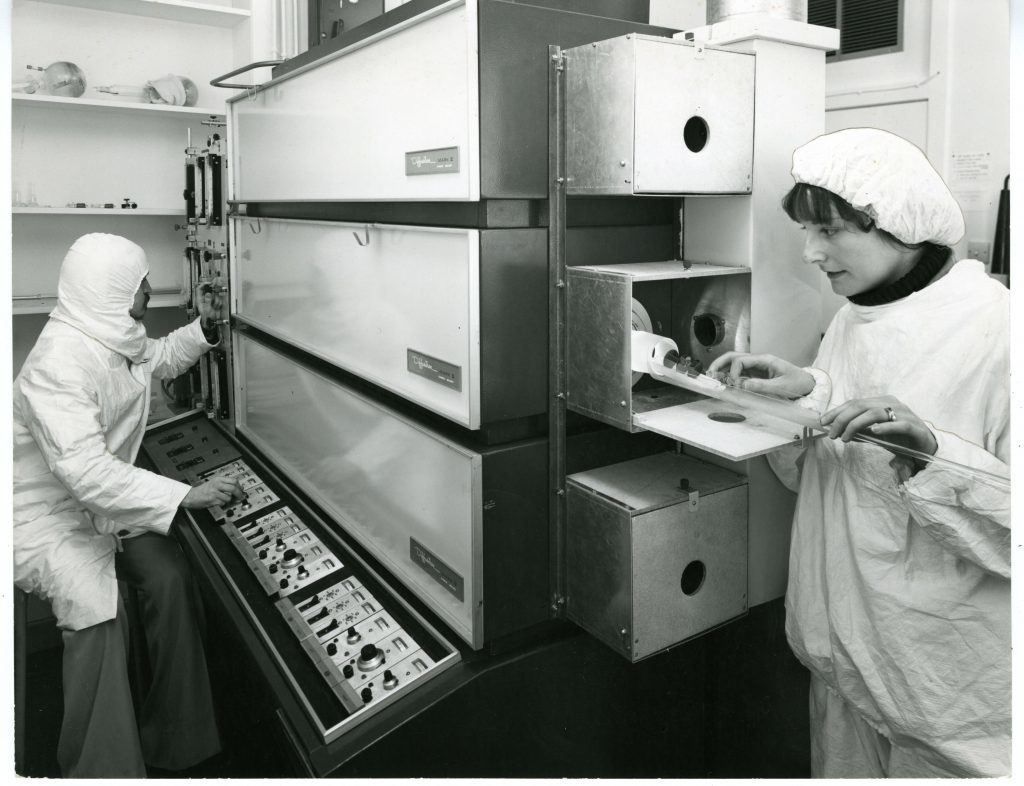 Mrs Catherine Woolridge and research student Mr Jim Boal operating the silicon defusion furnaces in the microelectronic lab clean room in the Dept of Electrical Engineering and Electronics, Dundee University, 1979 H254 1979-03-XX UoD Microelectronic Laboratory (C)UNKNOWN