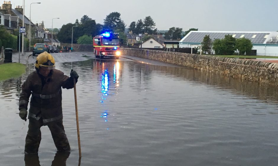 Firefighters work hard to unblock drains after flash floods in Ceres Road, Cupar