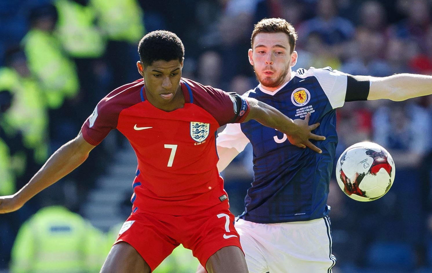 Andy Robertson competes with England's Marcus Rashford.
