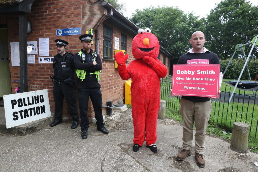 Candidate Bobby Smith arrives with Elmo as Police wait outside the polling station where Conservative Party leader Theresa May is expected to vote on