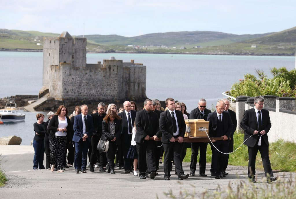 Funeral procession passes Kisimul Castle on its way to the Church of Our Lady, Star of the Sea, in Castlebay.