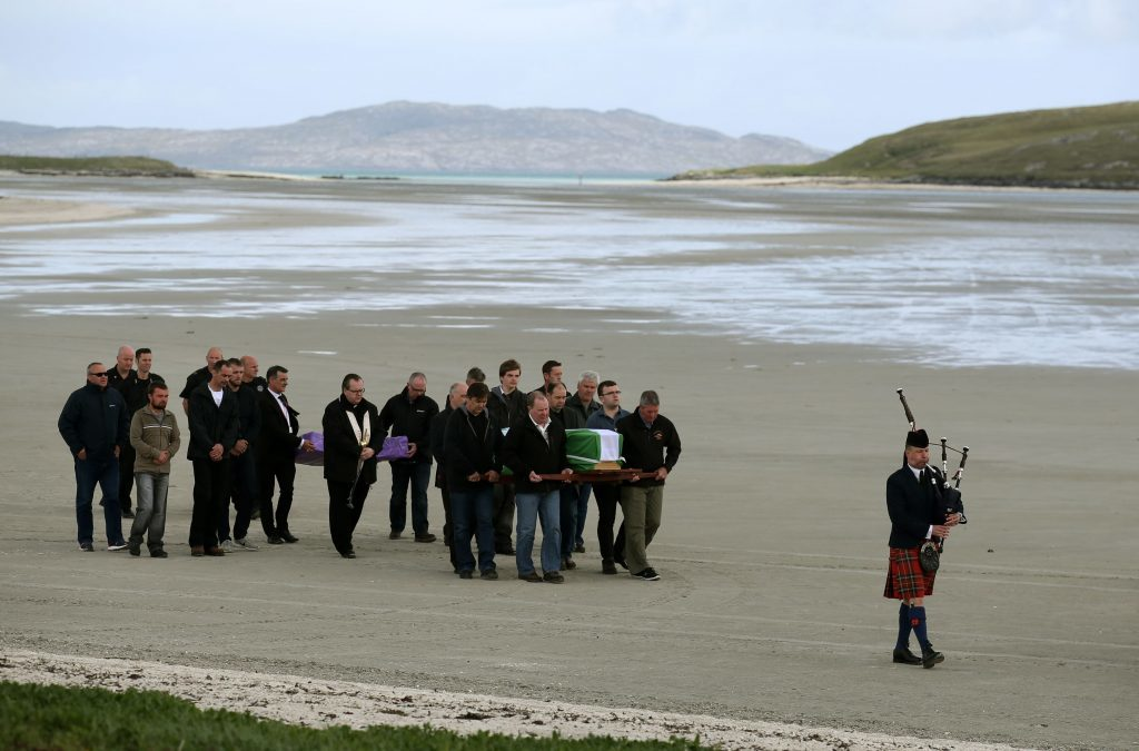 The coffin of Eilidh MacLeod draped in the Barra flag  is carried across Traigh Mhor beach at Barra airport after it arrived by chartered plane earlier.