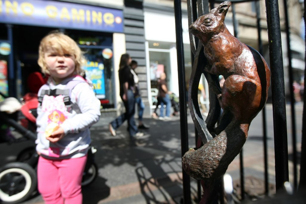 Iona Hail finds the bronze squirrel in a tree in Dundee's High Street.