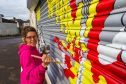 Painter Celie Byrne at a previously painter shutter in Kelty
