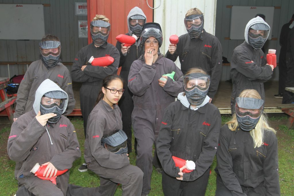 Students from Madras College in St Andrews flank Gayle ahead of a paintballing session.