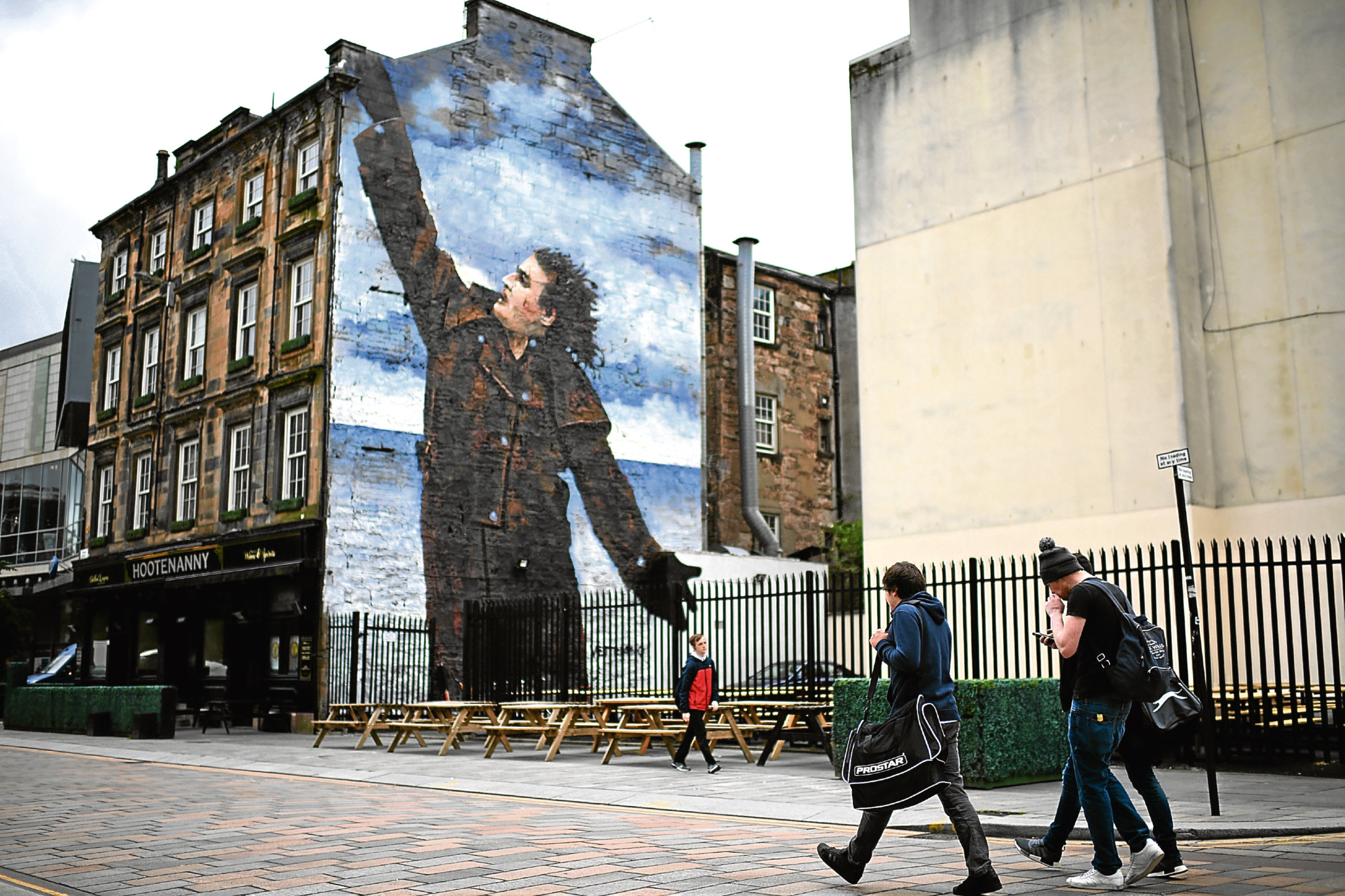 A mural of comedian Billy Connolly displayed on a gable wall in Glasgow.