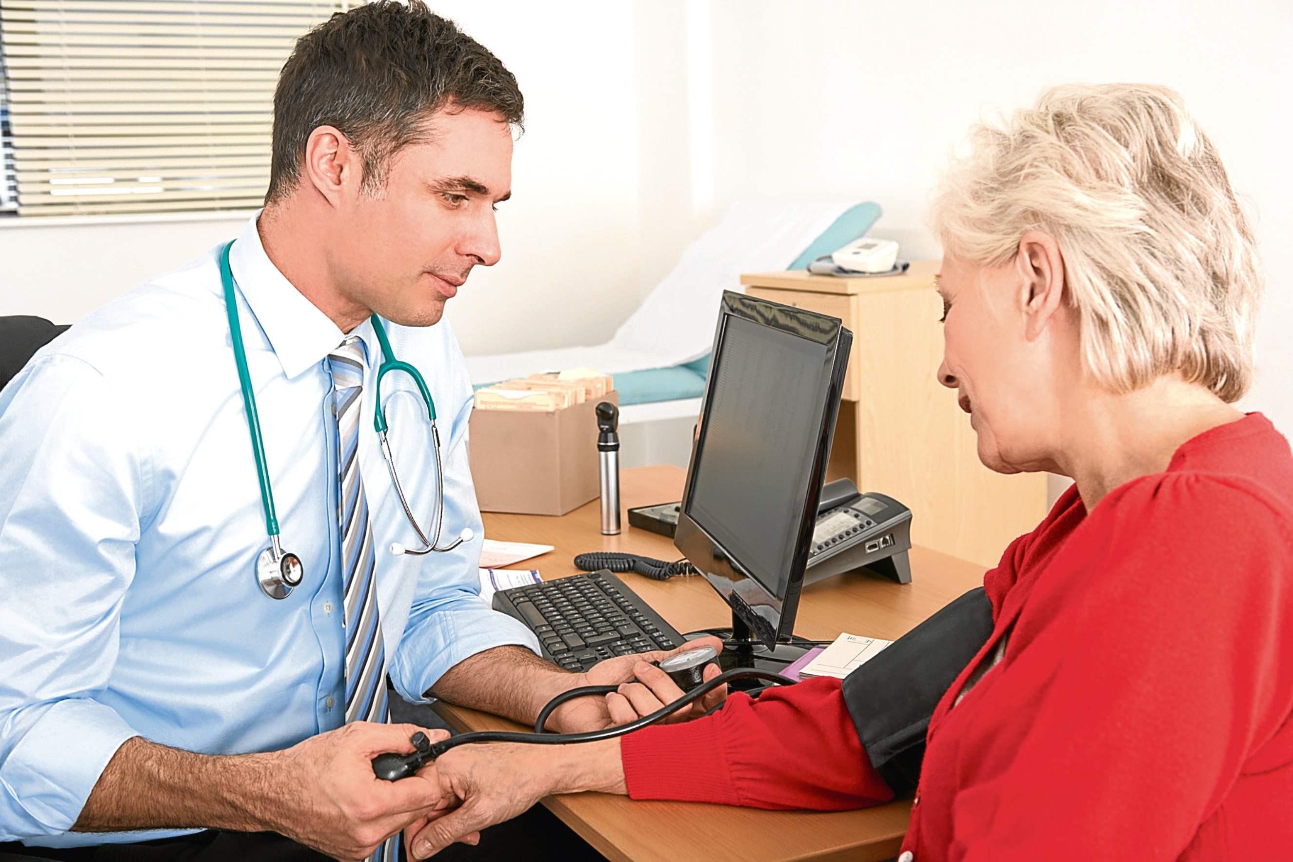 British doctor taking senior woman's blood pressure having a check up in consultation room