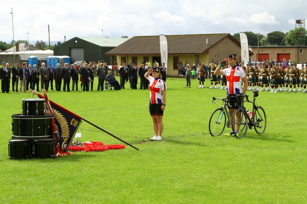 Officer Cadet Emily Whyte and WO1 Kevin Stacey of the cyclists who went from Crieff to Passchendaele, saluting after laying their wreath.