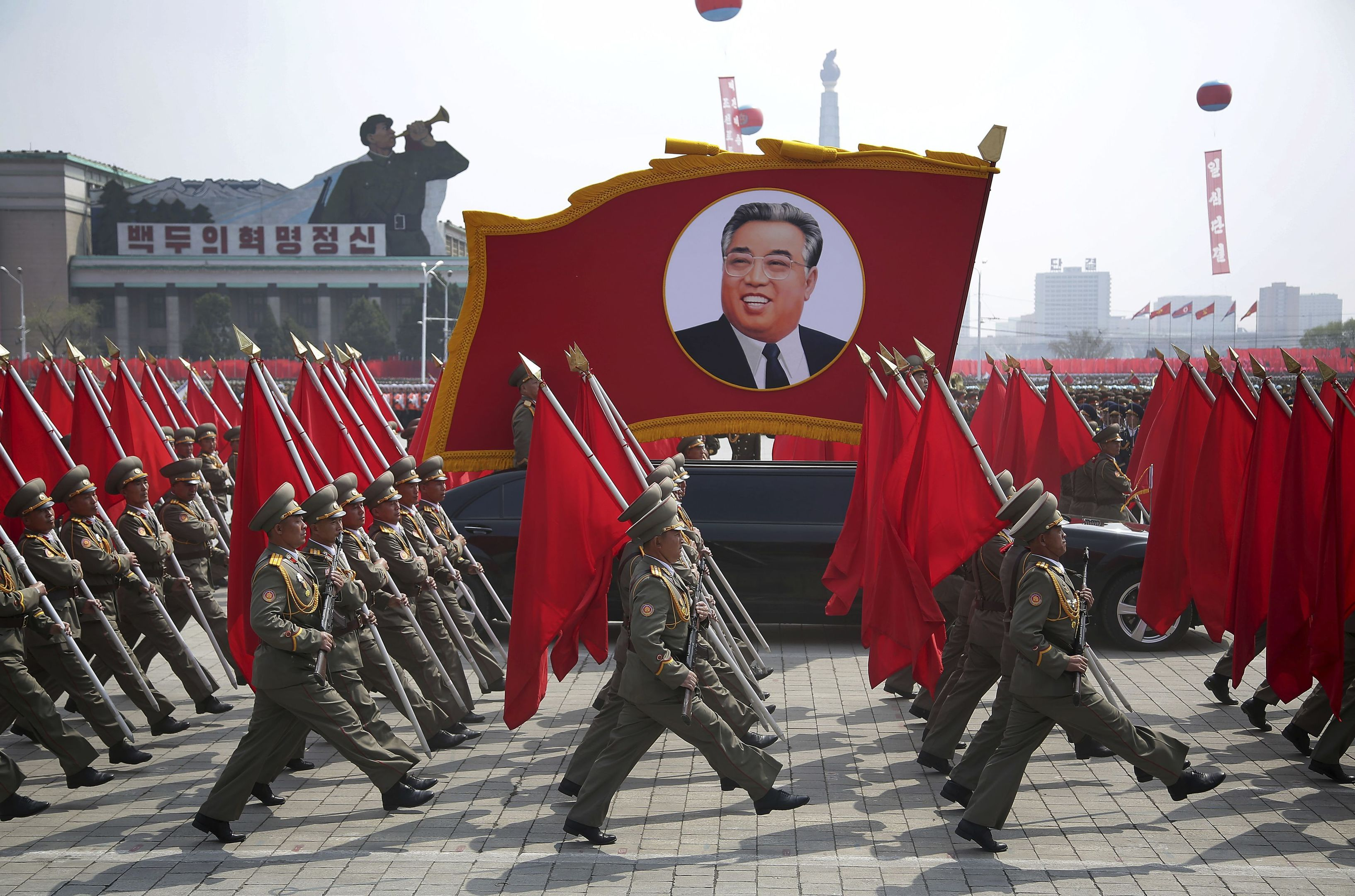 North Korean soldiers carry flags and a photo of late leader Kim Il Sung as they march across Kim Il Sung Square during a military parade.