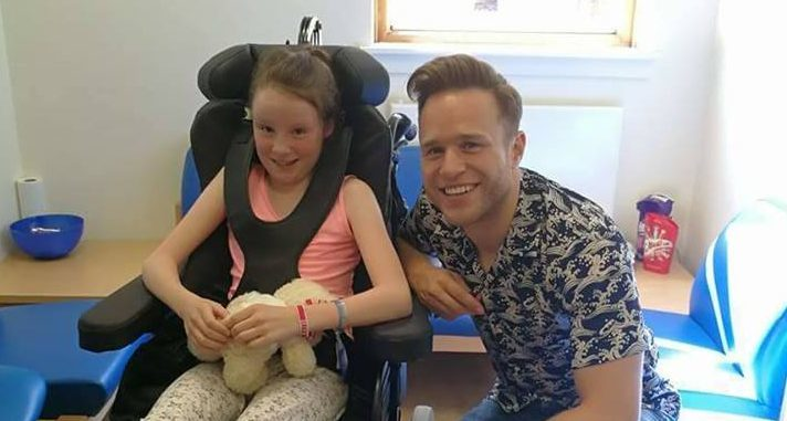 Olly posing with Emma during his surprise visit.