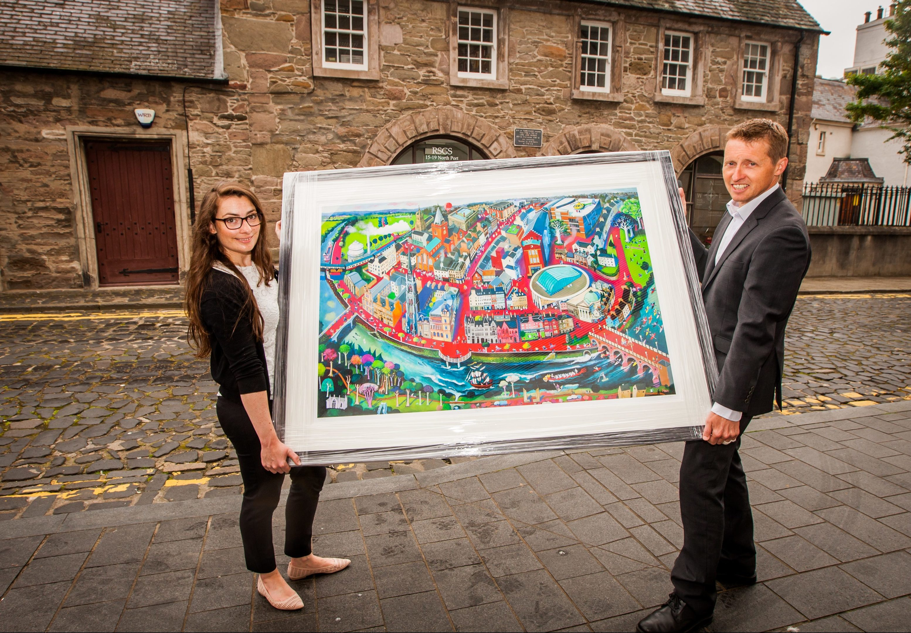 Gemma McDonald (RSGS communications officer) alongside chief executive, Mike Robinson and the painting 'Fair City' at the Royal Scottish Geographical Society, North Port, Perth.