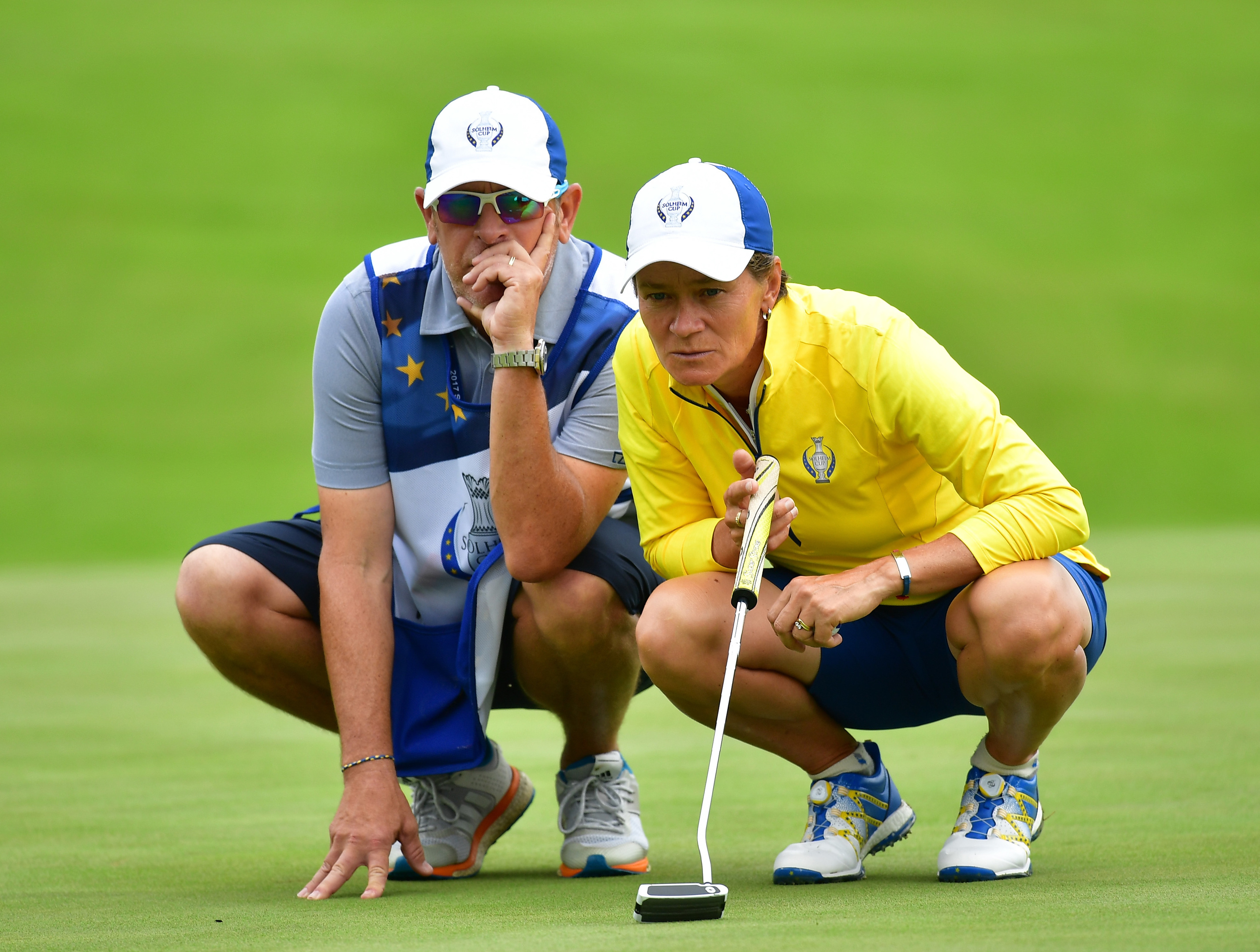 Catriona Matthew of Team Europe lines up a putt with caddie Mike Patterson during the second day morning foursomes matches of The Solheim Cup.