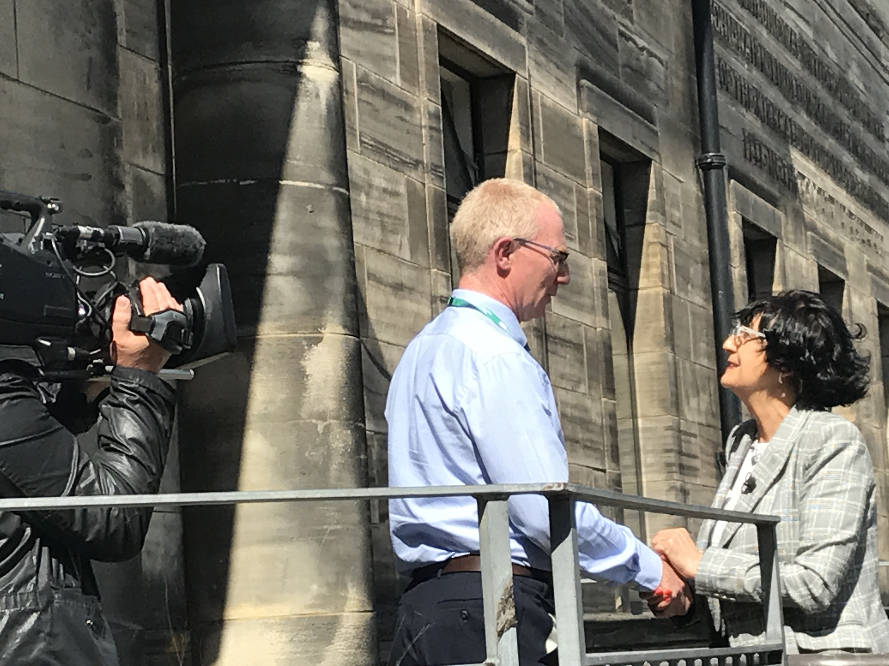 Collections curator Gavin Grant greets Anita Manning on the steps of Kirkcaldy Galleries.