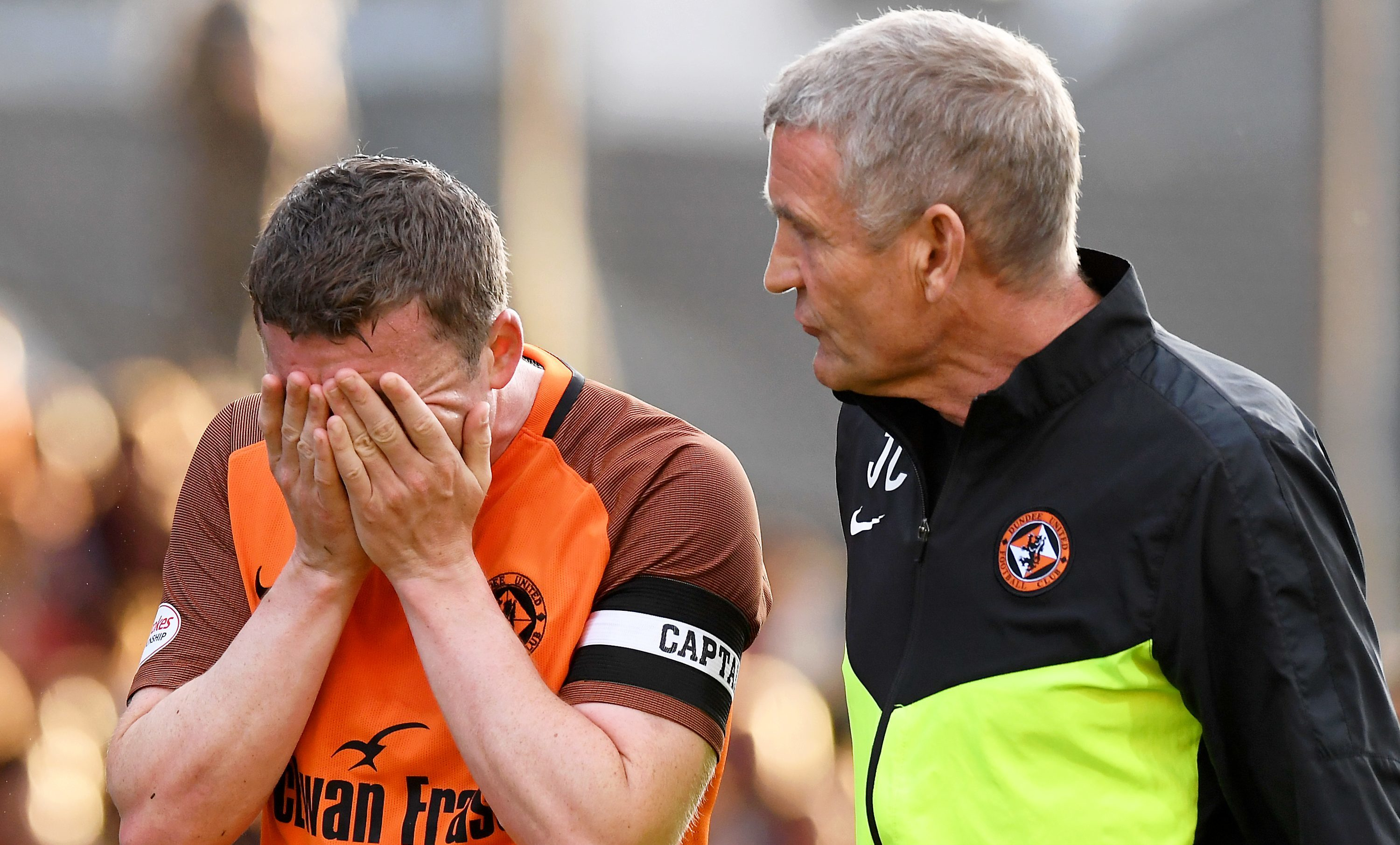 Tam Scobbie with United physio Jeff Clarke after suffering the injury.