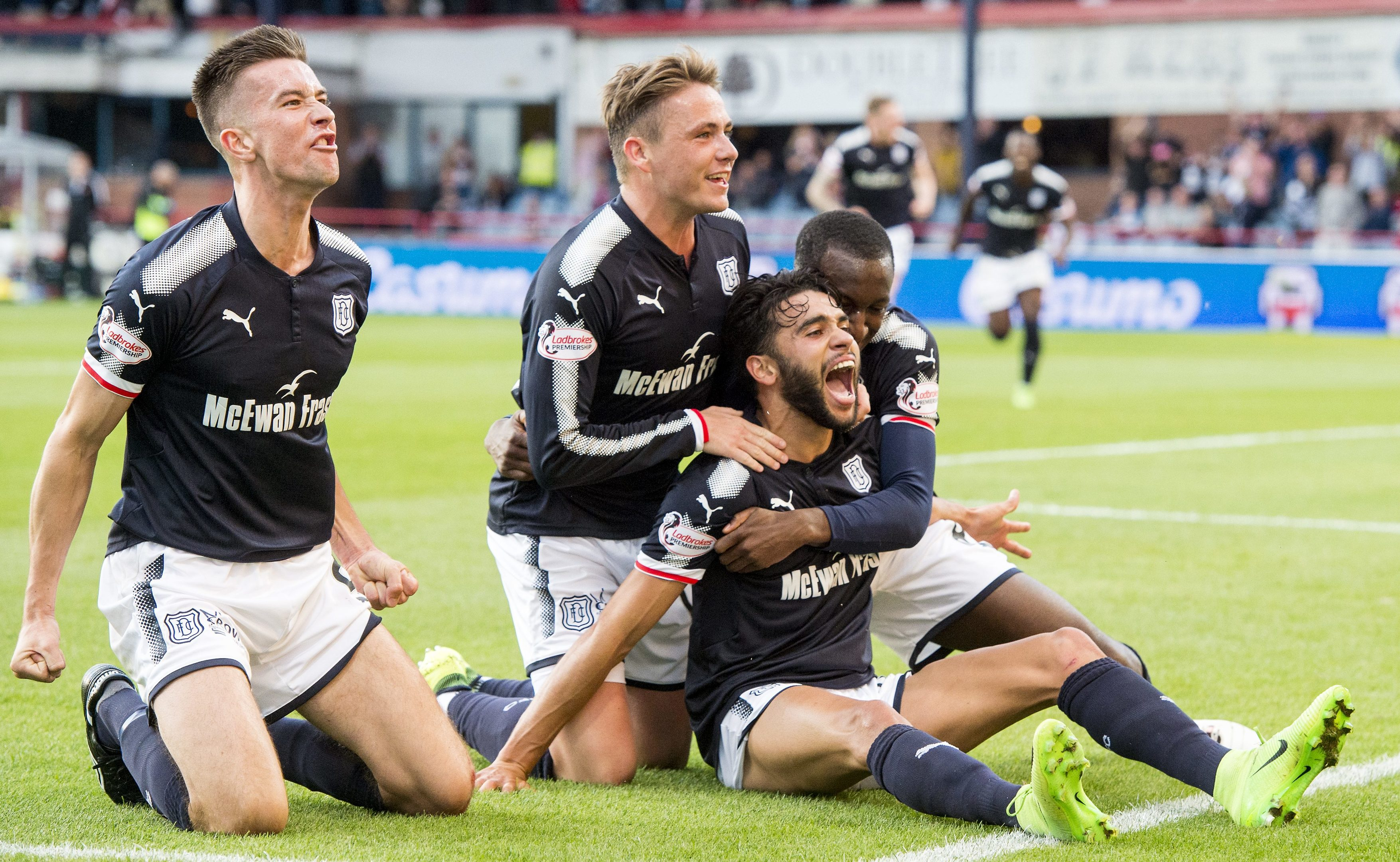 The Dundee players celebrate the opening goal.