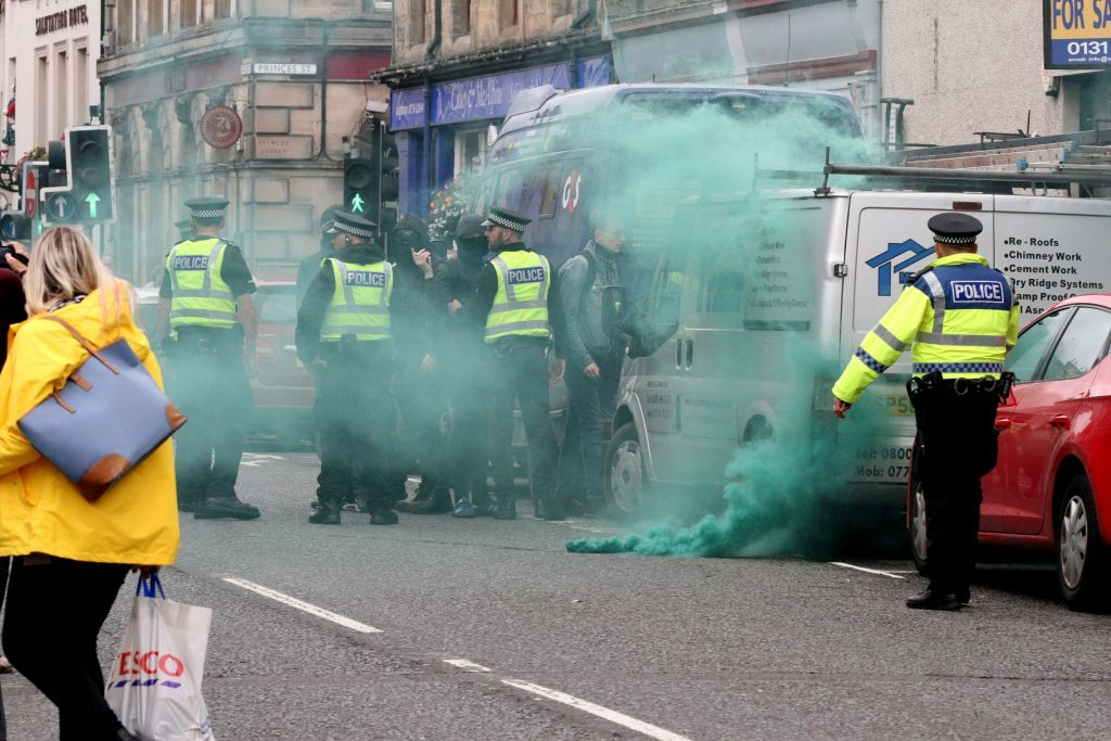 A gas canister is let off by a group protesting against the SDL
