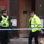 Police stand guard outside Dundee building one day on from man's death