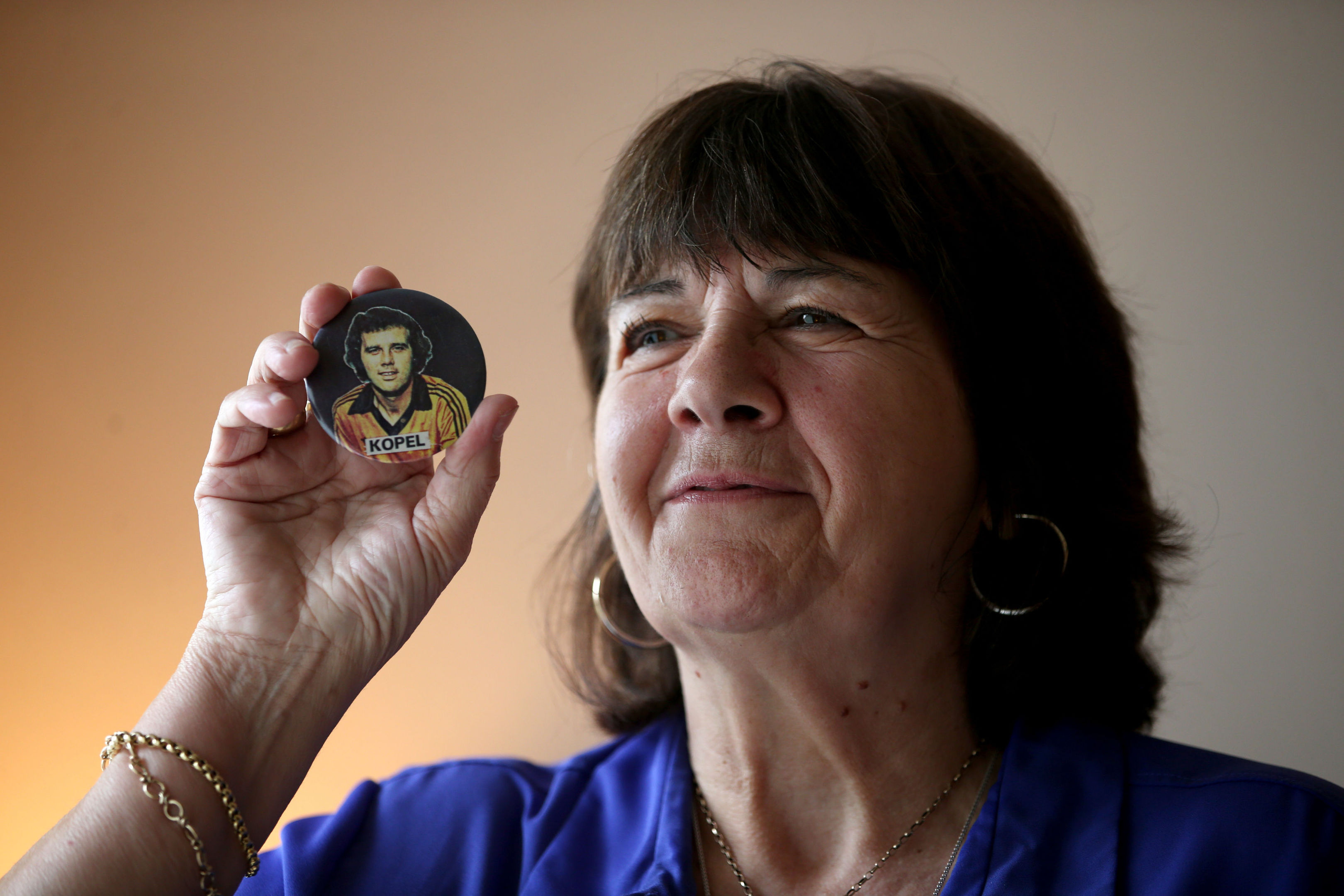 Amanda Kopel holds a football badge of her late husband Frank.