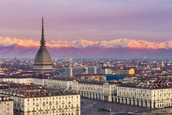 Torino (Turin, Italy): cityscape at sunrise with details of the Mole Antonelliana towering over the city and the snowcapped Alps in the background.