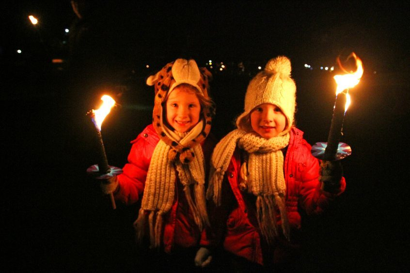 Twins Brooke & Bonnie Sturrock take part in the torch light parade.