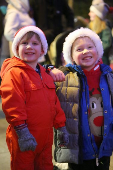 Ryan Dick and Lewis Atkinson in Santa hats in the square in Kirriemuir as the Christmas lights are switched on.
